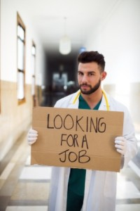 Young unemployed doctor holding a sign