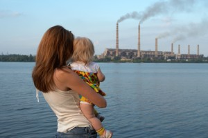 """care future"" concept. Young mother with her kids are looking at the chimney-stalks polluting an air"