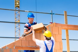 Two Bricklayer or builder or worker build or bricklaying or laying a stone or brick wall on construction or building site