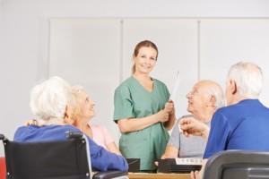 Frau als Krankenpfleger in Gruppe Senioren