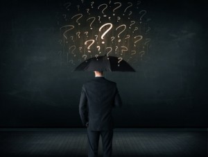 Businessman with umbrella and a lot of drawn question marks