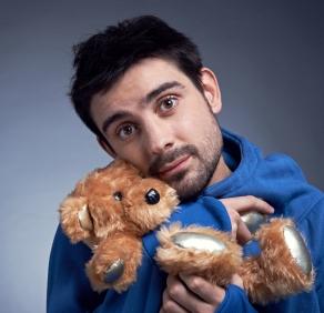Sad man embracing his teddy bear