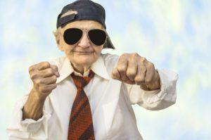 Funny elderly woman wearing cap in a fight pose.